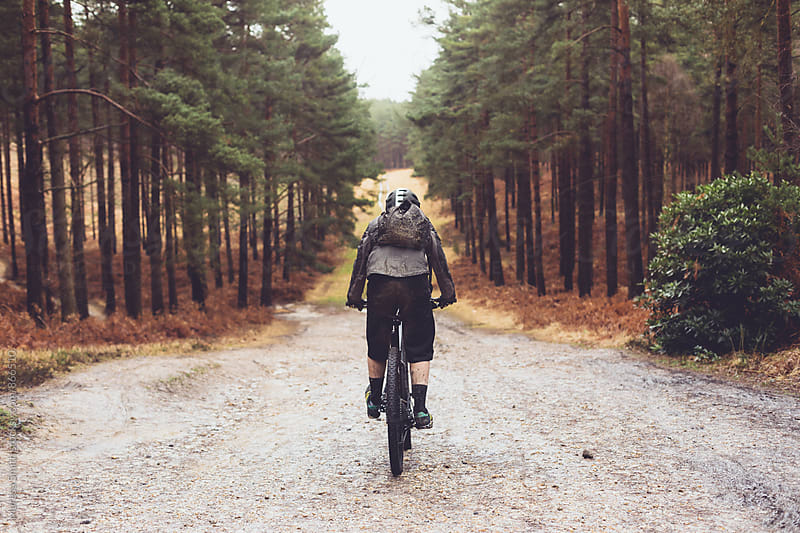 A man riding his bike down a wide gravel forest path by Maresa Smith for Stocksy United