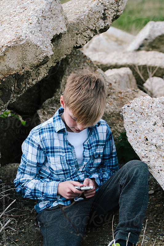 Trendy young boy sitting on a pile of rubble on waste ground. Texting. by Helen Rushbrook for Stocksy United