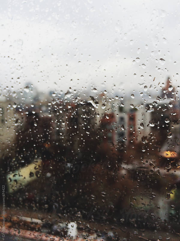 A view of a busy stormy city through a window full of rain drops by Greg Schmigel for Stocksy United
