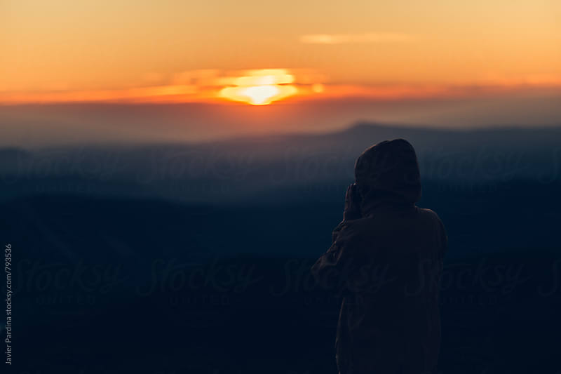 silhouette of girl taking photos at sunset by Javier Pardina for Stocksy United