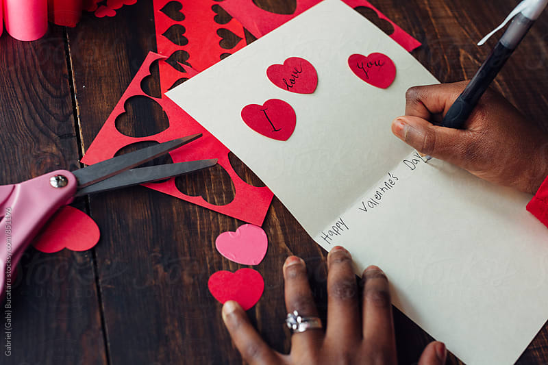 African American girl's hand writing a valentine card by Gabriel (Gabi) Bucataru for Stocksy United