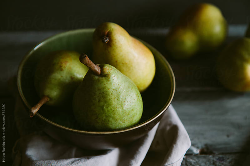 Pears in a bowl. Dark light. by Helen Rushbrook for Stocksy United