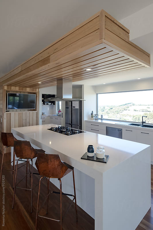 Architect designed kitchen with copper bench stools by Rowena Naylor for Stocksy United
