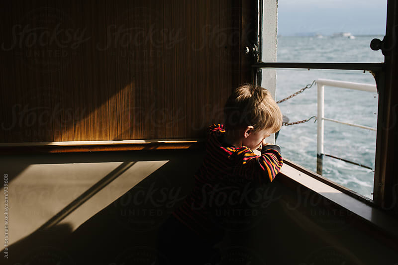 A boy rubs his eyes as he looks out of the window while travelling by ferry. The afternoon sun illuminates the wooden partition behind him.   by Julia Forsman for Stocksy United