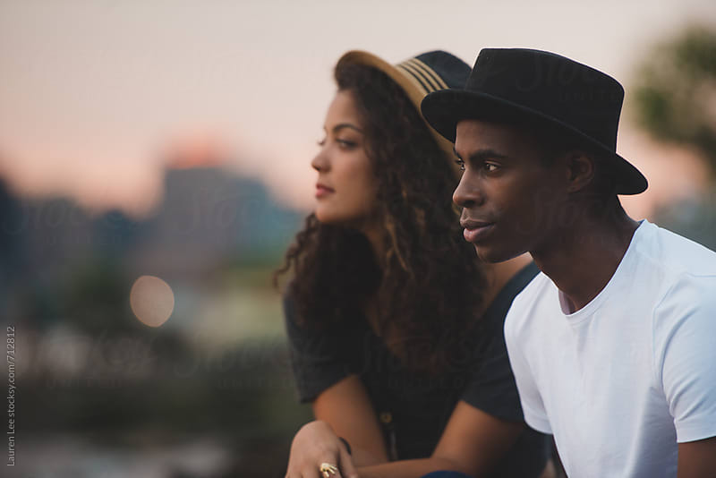 Young man and woman watching sunset by Lauren Naefe for Stocksy United