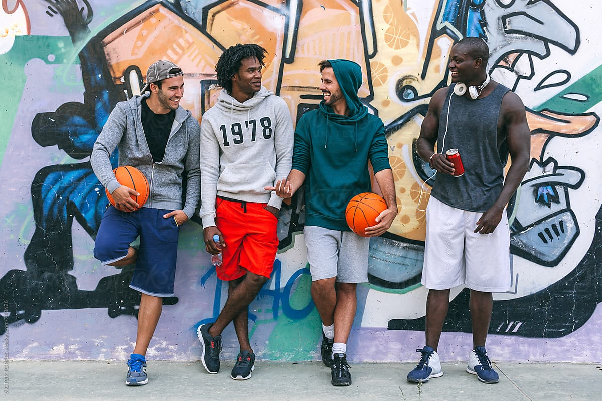 Friends Rests Over A Graffiti Painted Wall After A Street Basketball Game By Victor Torres Stocksy United