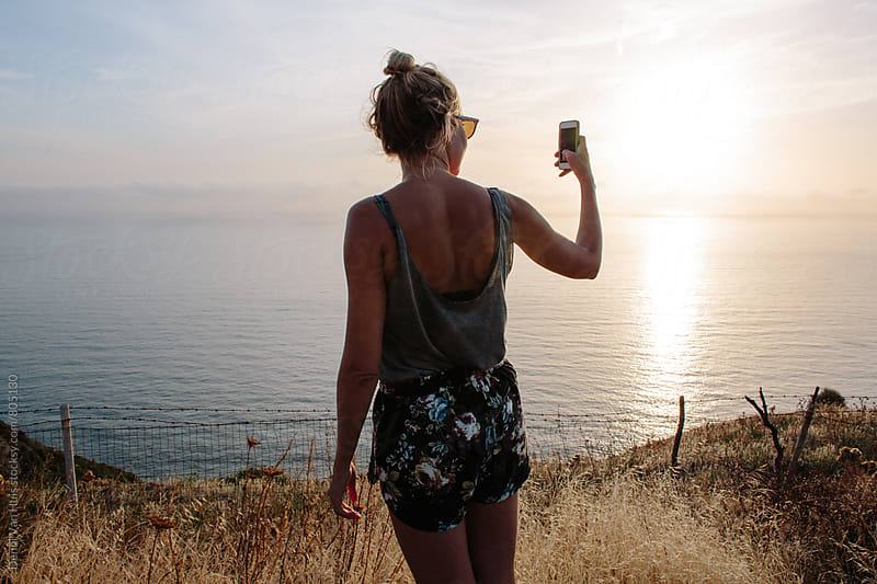 Woman using phone to take a picture of a beautiful view by Denni Van Huis for Stocksy United