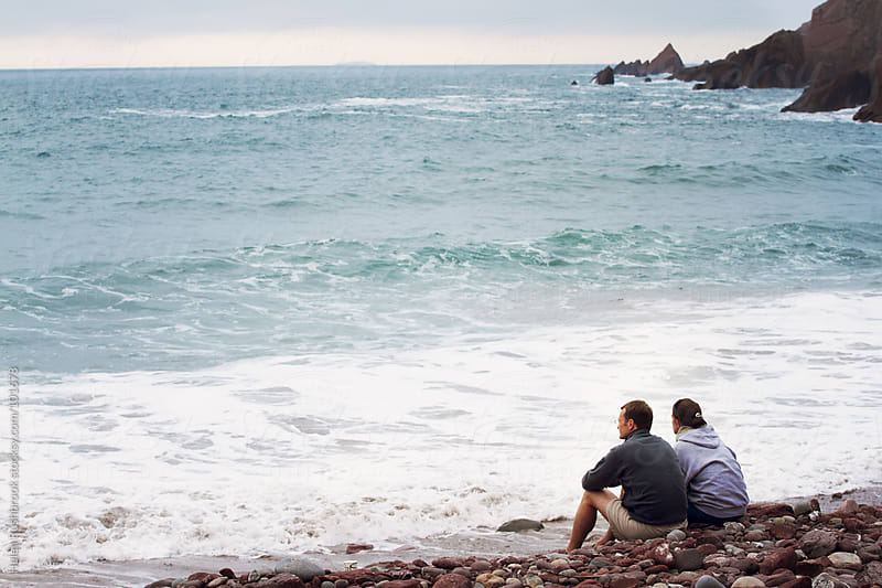 A couple sitting on a beach looking out to sea by Helen Rushbrook for Stocksy United