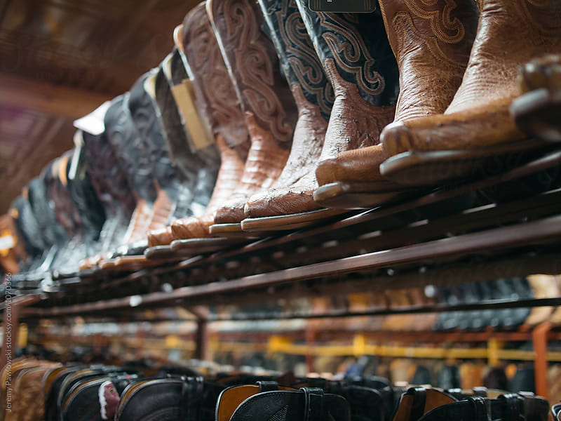 Line of leather cowboy boots in western wear shop by Jeremy Pawlowski for Stocksy United