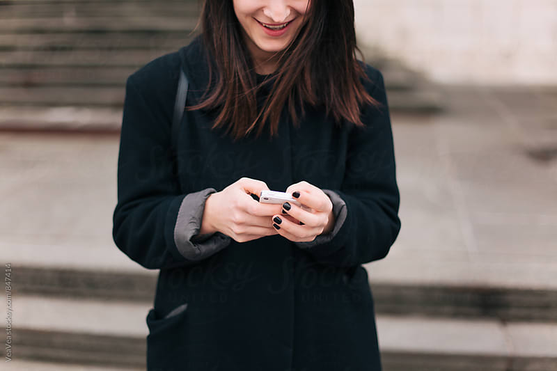 Happy woman using her mobile phone in the street by Marija Mandic for Stocksy United