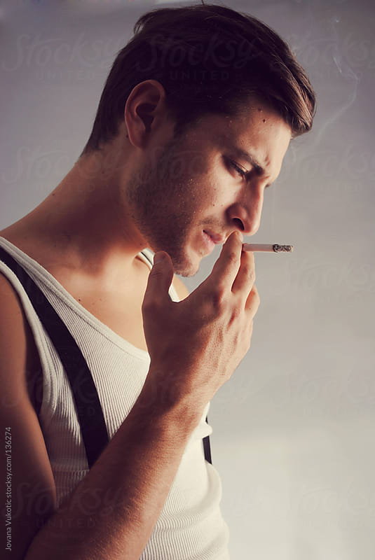 young man smoking by Jovana Vukotic for Stocksy United