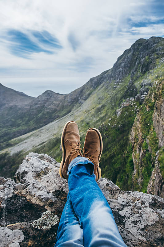 leather shoes and jeans of a hiker sitting on a mountain top by Micky Wiswedel for Stocksy United
