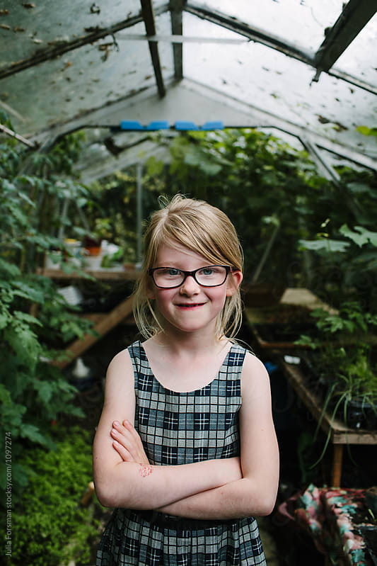 Portrait of cheeky girl wearing glasses with her arms crossed. by Julia Forsman for Stocksy United