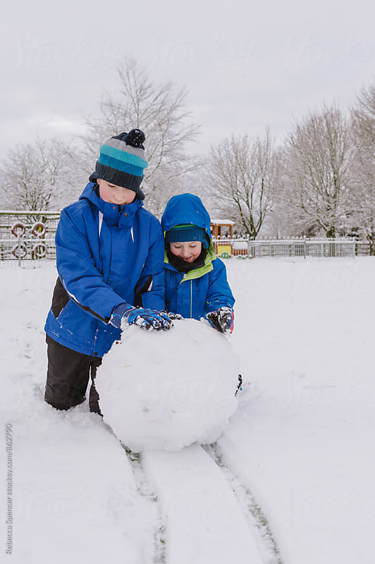 Brothers rolling a large snowball by Rebecca Spencer for Stocksy United
