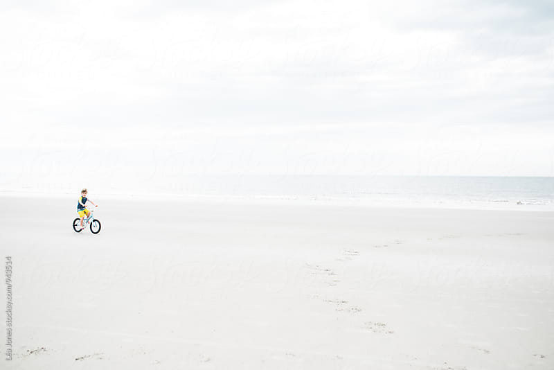 little boy riding his bike on the beach by Léa Jones for Stocksy United