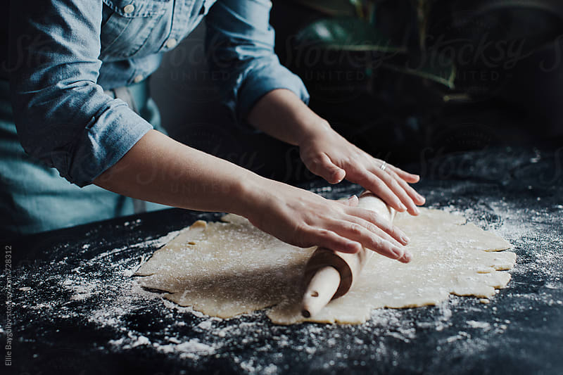 Woman rolling a pie dough by Ellie Baygulov for Stocksy United