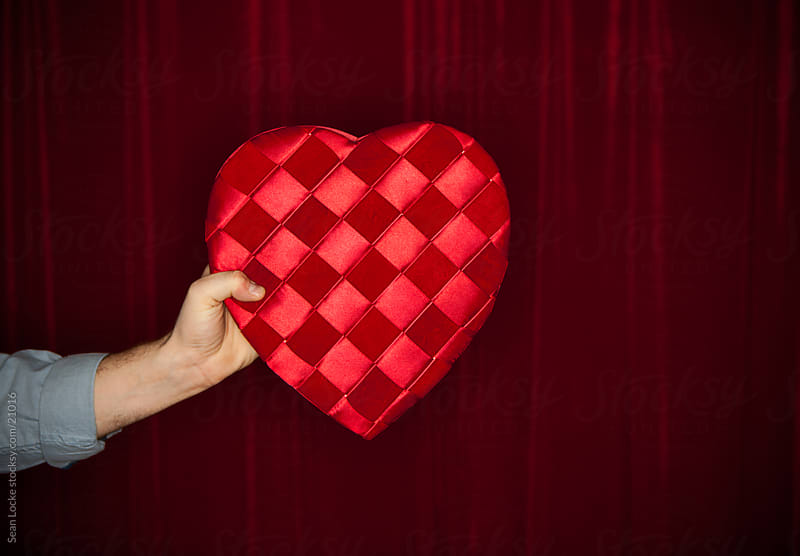 Valentine: Man Holding Heart Shaped Box of Candy by Sean Locke for Stocksy United