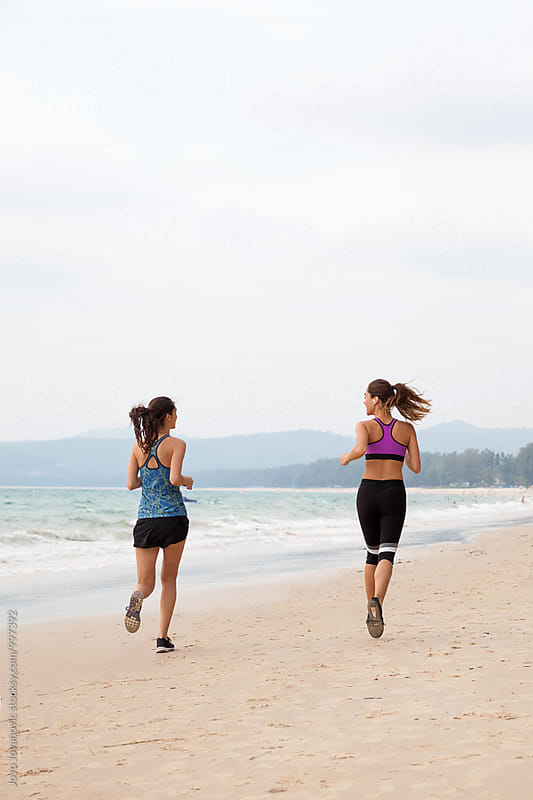 Two girlfriends running together at the beach by Jovo Jovanovic for Stocksy United