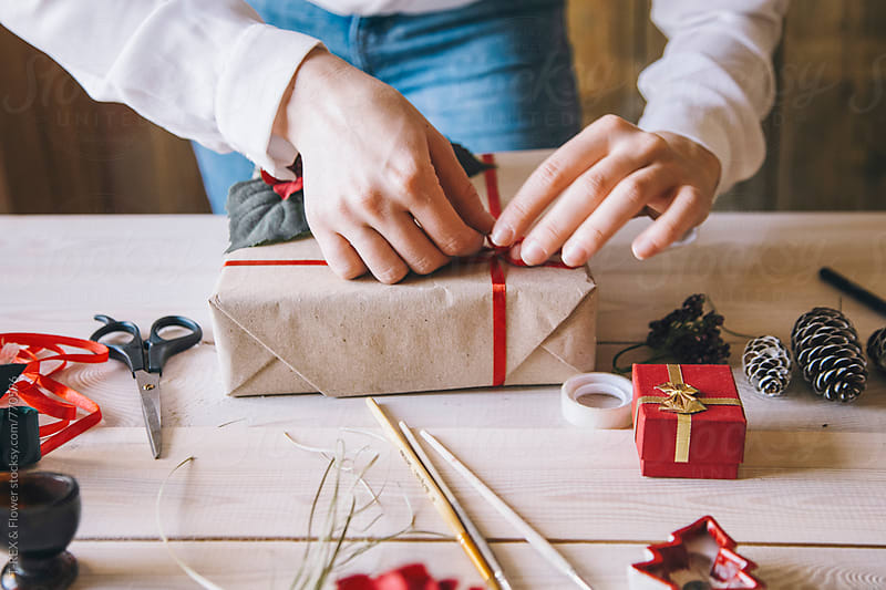 Woman decorating Christmas present by Danil Nevsky for Stocksy United