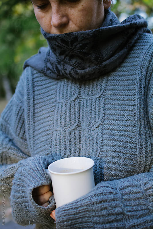 Woman holding warm drink by Pixel Stories for Stocksy United