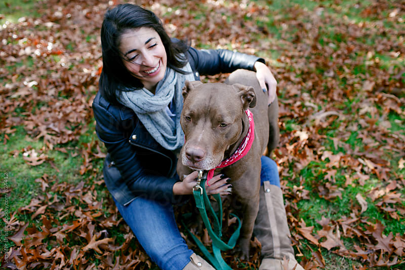Woman sitting with dog in leaves by Jennifer Brister for Stocksy United