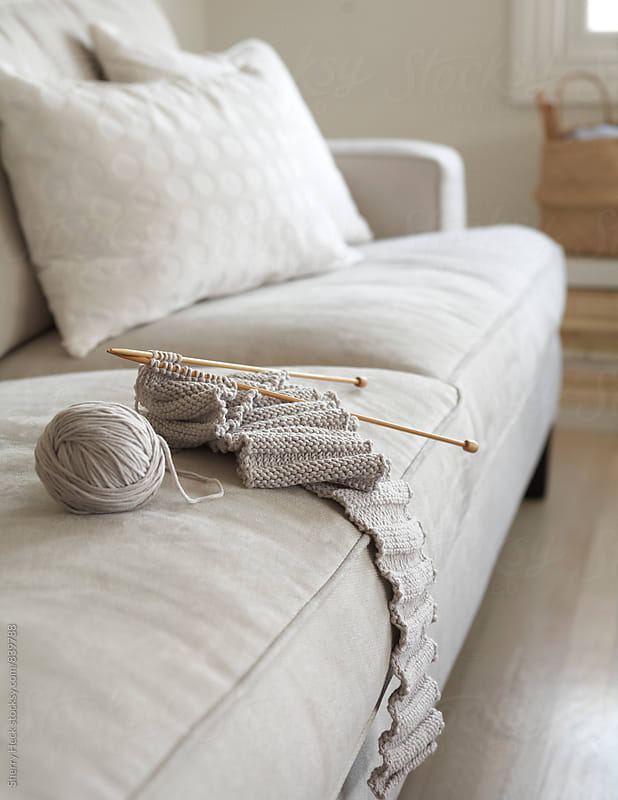 Knit Scarf laying on sofa in an all beige living room by Sherry Heck for Stocksy United