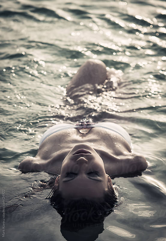 Beautiful young woman floating in the water by Mark Korecz for Stocksy United