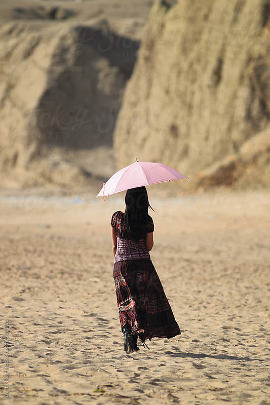 Young girl with umbrella  by Yasir Nisar for Stocksy United