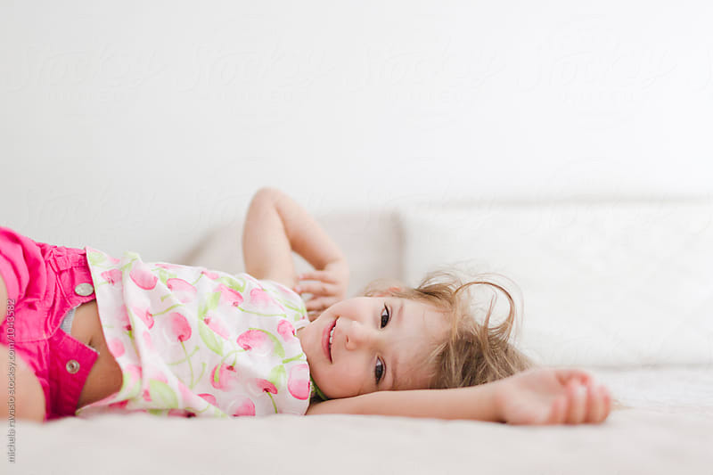Cute little girl lying on bed by michela ravasio for Stocksy United