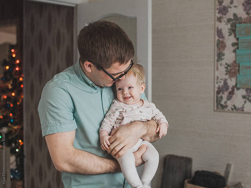 Father holding his baby daughter by Irina Efremova for Stocksy United