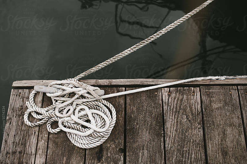 ropes tied down to dock by the water by Nicole Mason for Stocksy United