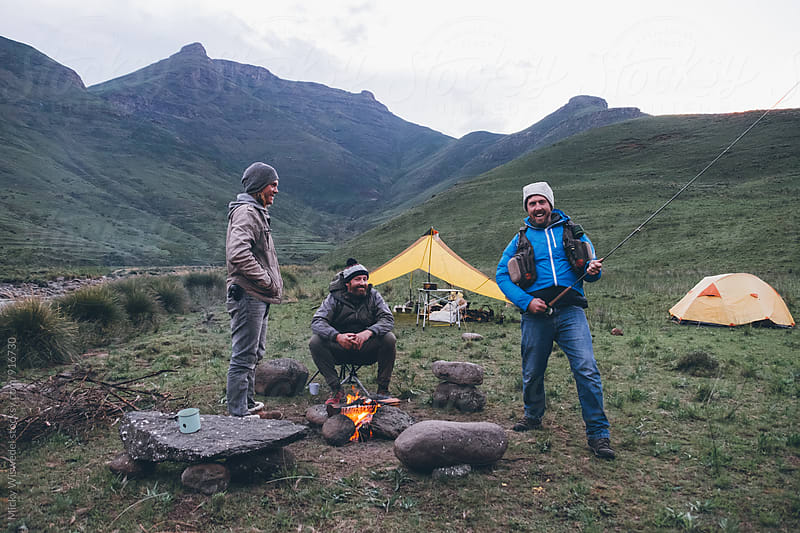 flyfishermen friends fooling around by a camp fire in the mountains by Micky Wiswedel for Stocksy United