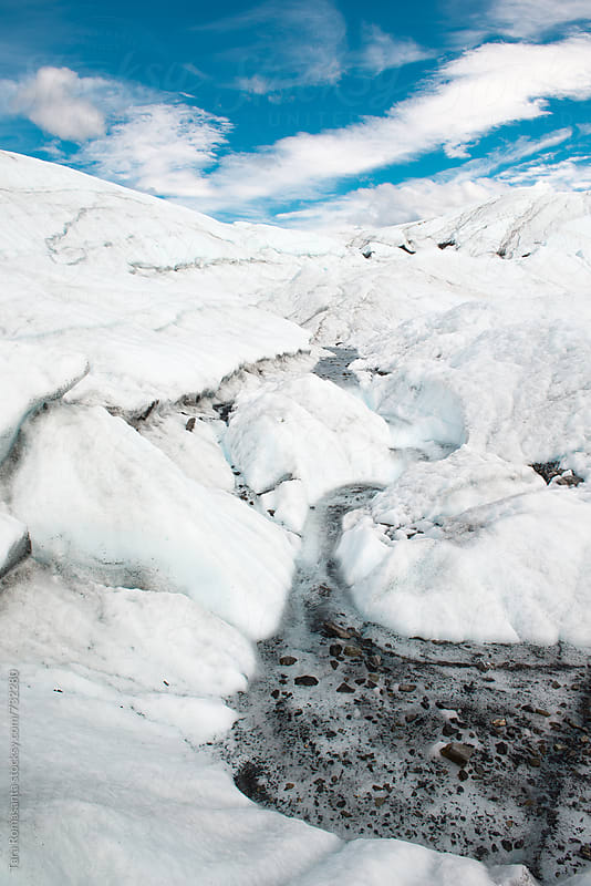 snow melt and silt at the base of a glacier by Tara Romasanta for Stocksy United