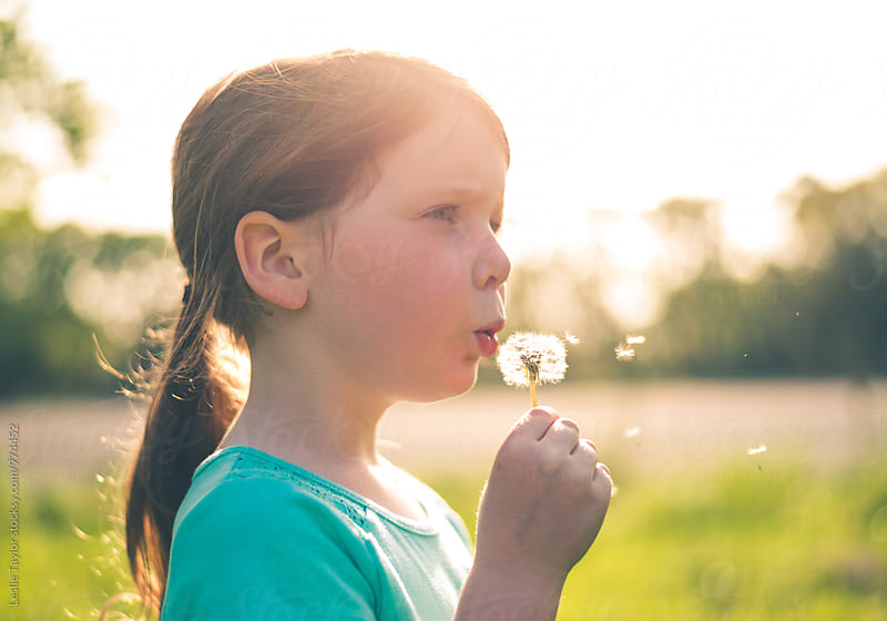Girl Blowing Dandelion In The Sun by Leslie Taylor for Stocksy United