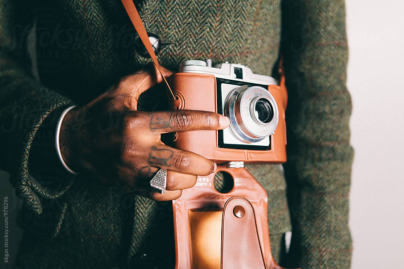 Close up of tattooed black hands holding a vintage camera by kkgas for Stocksy United