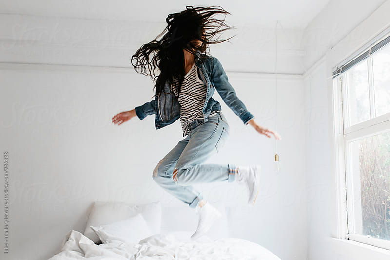 Girl jumping on bed by luke + mallory leasure for Stocksy United