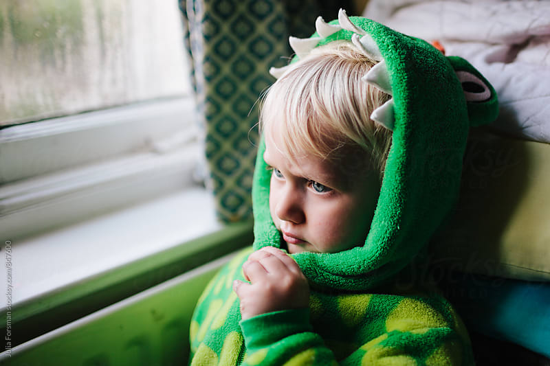 A little child dressed as a dragon taking some time out. by Julia Forsman for Stocksy United