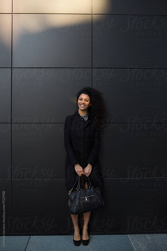 Portrait of young mixed business woman smiling at the camera by michela ravasio for Stocksy United