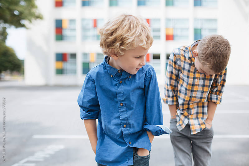 Two boys standing in front of a school with hands in pockets by Ania Boniecka for Stocksy United