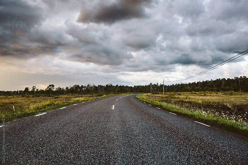 Storm clouds over empty country road by Lior + Lone for Stocksy United