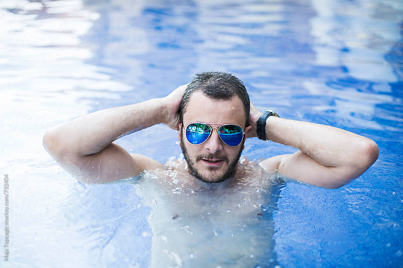 Young man wearing sunglasses relaxing in the pool by Maja Topcagic for Stocksy United
