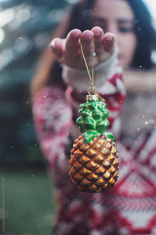 A young woman holding a Christmas ornament of a pineapple by Chelsea Victoria for Stocksy United