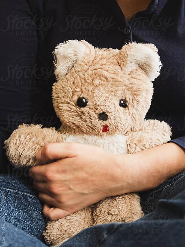 Person holding on to a teddy bear by Melanie Kintz for Stocksy United
