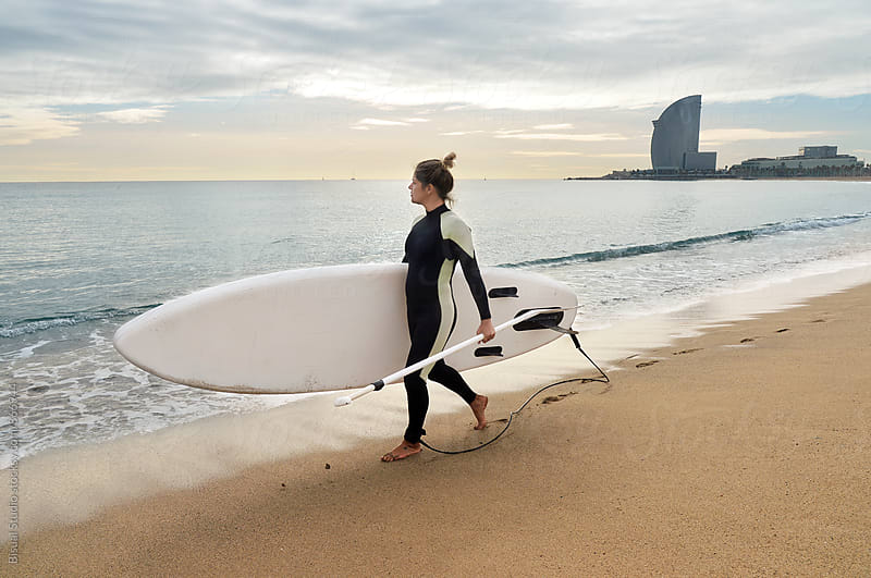Blonde girl walking with her paddle board in Barcelona beach by Bisual Studio for Stocksy United