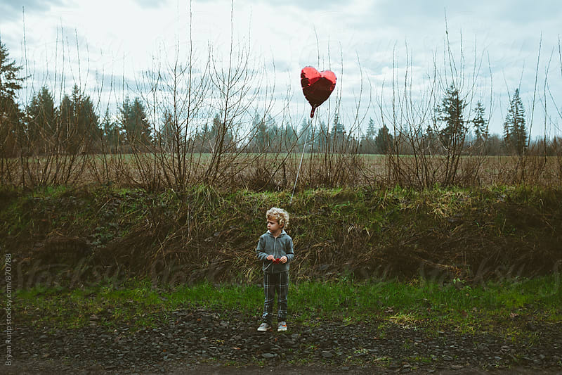 Little Boy Holding Heart Balloon in a Field by Bryan Rupp for Stocksy United