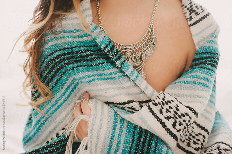 Young girl wearing bohemian necklace wrapped in mexican pattern blanket by Daring Wanderer for Stocksy United