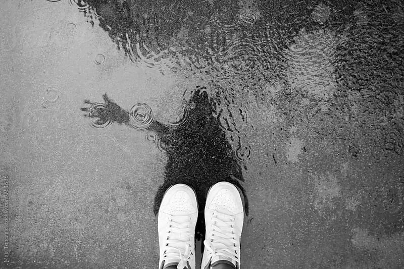 Female white sneakers in the pond of rain by Maja Topcagic for Stocksy United