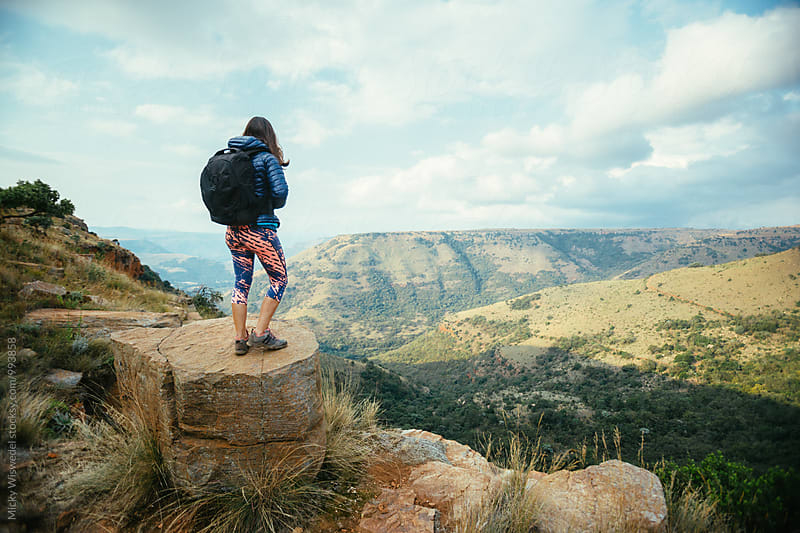 Hiker on a rocky outcrop overlooking a scenic mountain valley by Micky Wiswedel for Stocksy United