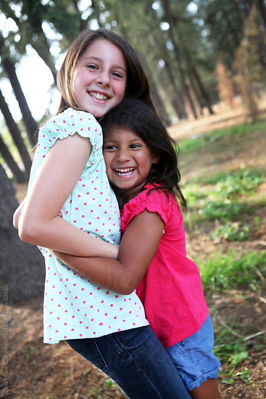 Two girls hugging in park while laughing by Dina Giangregorio for Stocksy United