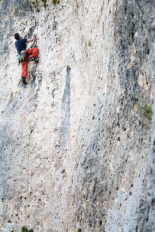 Rock climber climbing a vertical wall outdoors  by Jovana Milanko for Stocksy United